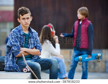 Upset boy and happy couple of teens apart on the street