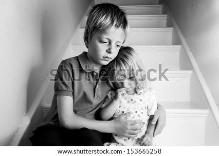 Upset Brother comforting his baby sister. - stock photo