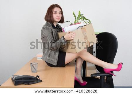 Upset business woman carrying office belongings after loosing job - stock photo