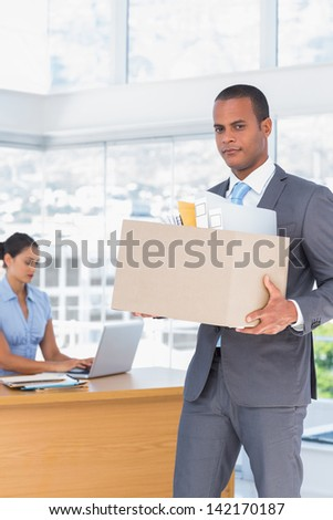 Upset businessman leaving the company while holding a box with his stuff