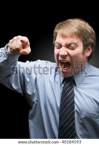 Upset businessman yelling on dark background focus on face - stock photo