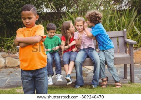 Upset child standing away from group sitting on a bench - stock photo