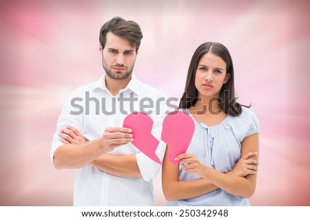 Upset couple holding two halves of broken heart against digitally generated pink girly design - stock photo