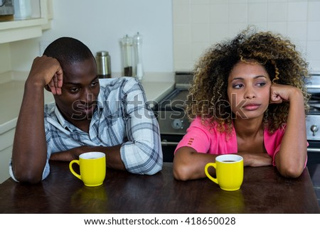 Upset couple ignoring each other after fight at home - stock photo