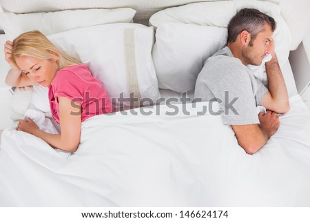 Upset couple lying back to back in bed - stock photo