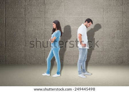 Upset couple not talking to each other after fight against grey room - stock photo