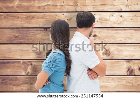 Upset couple not talking to each other after fight against wooden planks background - stock photo