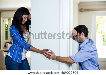 Upset couple standing on opposite sides of the wall and holding hands - stock photo