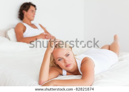 Upset cute couple in their bedroom - stock photo