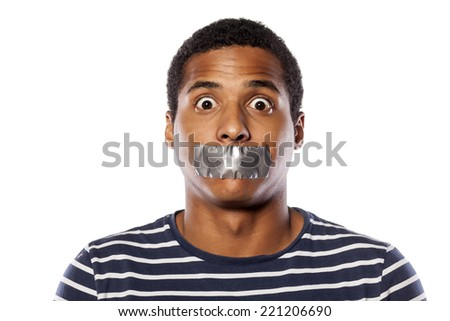 upset dark-skinned young man with adhesive tape over his mouth - stock photo