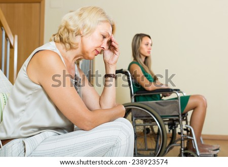 Upset elderly woman and handicapped female having domestic quarrel - stock photo