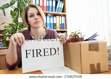 "Upset employee with collected things and sheet of paper with word ""Fired"""