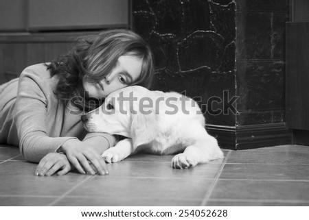 Upset girl with her friend, golden retriever. Monochrome photo - stock photo