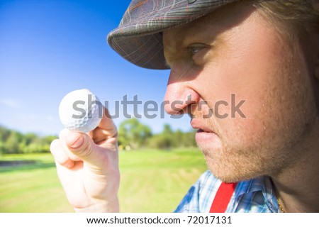 Upset Golfer Has A Mid Game Crisis While Arguing With The Golf Ball He Is Holding In A Funny And Humorous Sport Concept - stock photo
