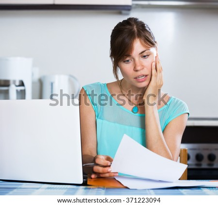 Upset housewife reading banking statement