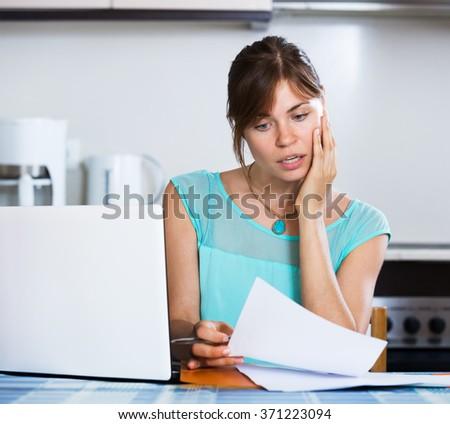 Upset housewife reading banking statement - stock photo
