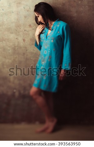 Upset indian girl in blue dress standing against stone background. Offened upset indian girl against wall.  Dissapointed east girl in blue dress.  - stock photo