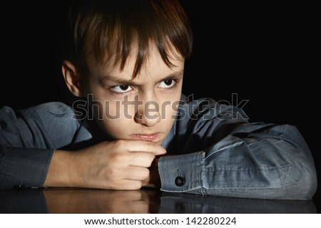 upset little boy on a black background - stock photo
