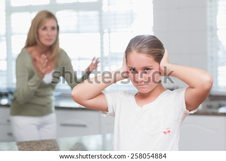 Upset little girl covering her ears while her mother screaming at home in the kitchen - stock photo