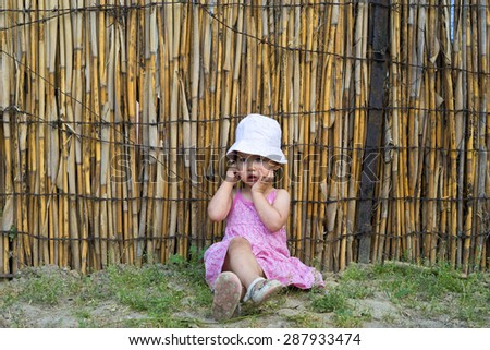 upset little girl covering her mouth with palms and looking aside - stock photo