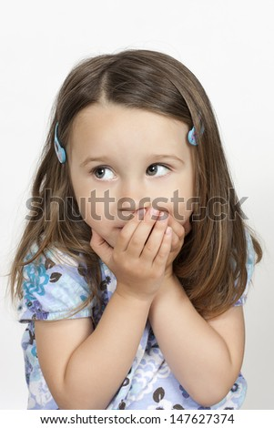 upset little girl covering her mouth with palms and looking aside with afraid expression on her scared face - stock photo