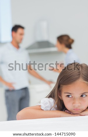 Upset little girl listening to parents who are arguing in the kitchen