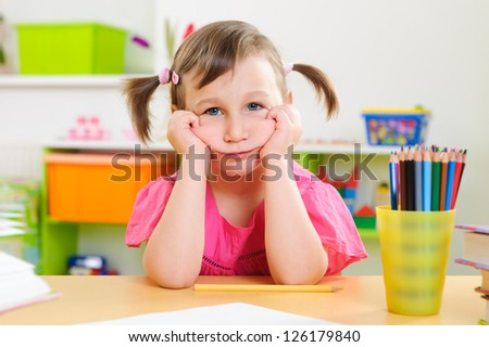Upset little girl sitting with colorful pencils at desk - stock photo
