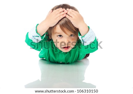 Upset little kid, 2 years old boy, sitting on the floor on his belly, putting hands on his head, showing he is in trouble. High resolution image isolated on white background . Studio shot.