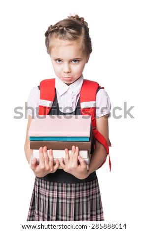 Upset little schoolgirl in uniform standing on white background and holding books  - stock photo