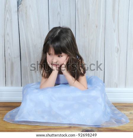 upset little sitting girl with hands on face - stock photo
