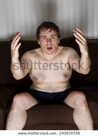 Upset man at what he is watching on the TV - stock photo