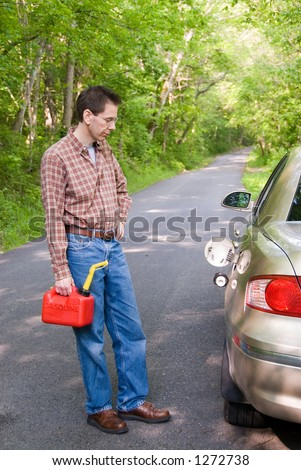 Upset man holding a gas can on a country road, staring at the empty gas tank of his car. - stock photo