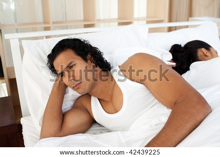 Upset man in bed sleeping separate of a woman after having an argument