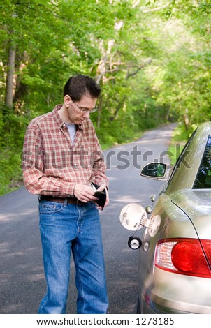 Upset man on a country road, staring in his wallet to see if he has the money to fill the empty gas tank of his car and pay for the tow truck when it arrives. - stock photo