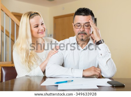 Upset man sitting with credit certificate, wife standing near  - stock photo