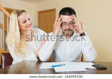 Upset man sitting with the credit certificate, wife standing near  - stock photo