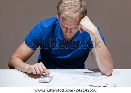 Upset man with financial problems using calculator - stock photo