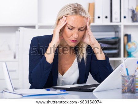 Upset mature businesswoman with headache working with documents in office