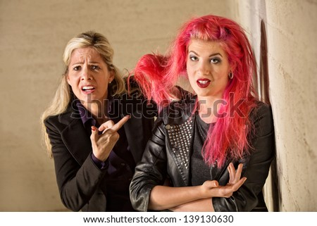 Upset mother holding teenage girls pink hair - stock photo