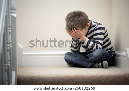 Upset problem child with head in hands sitting on staircase concept for bullying, depression stress or frustration - stock photo