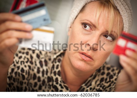 Upset Robed Woman Glaring At Her Many Credit Cards. - stock photo