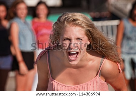 Upset screaming young white teenager with group - stock photo