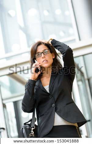 Upset stressed businesswoman on cellphone. Anxious woman on business crisis receiving bad financial news outside city corporate building. Hispanic female executive suffering stress and anxiety. - stock photo