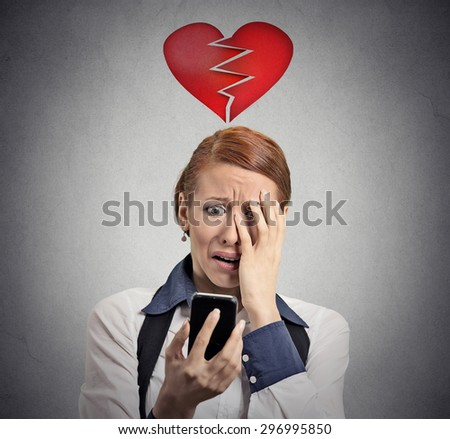 Upset stressed frustrated woman looking at cellphone disgusted with message she received isolated on gray background. Sad human face expression emotion feeling reaction perception body language - stock photo