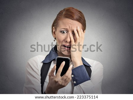Upset stressed woman holding cellphone disgusted shocked with message she received isolated grey background. Funny looking human face expression emotion feeling reaction life perception body language - stock photo