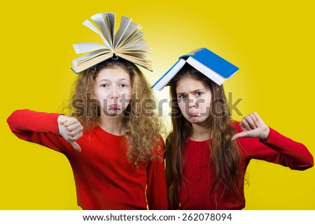 Upset Two sisters , little schoolgirl  with thumb down and books on their head, isolated over yellow background.  - stock photo