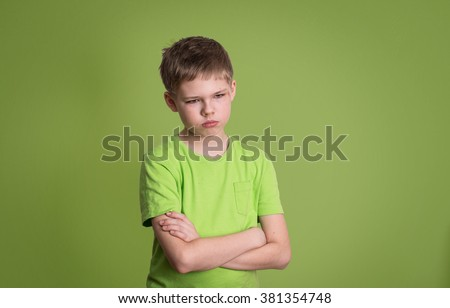 Upset unhappy angry kid with arms crossed, scratch on his face, isolated on green background. - stock photo