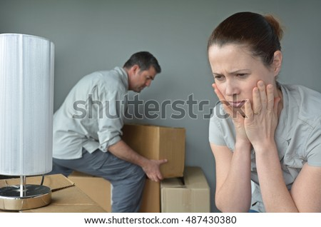 Upset woman (age 30-40) do not want to move to a new home. Moving house concept. Real people. copy space