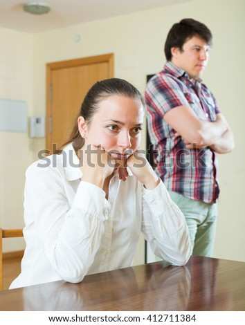 Upset woman and guy during conflict in living room at home