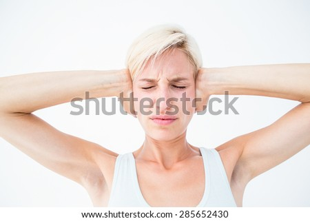 Upset woman covering her ears on white background - stock photo